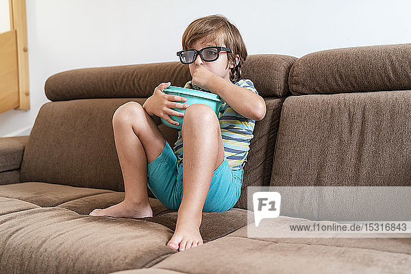 Boy sitting on couch at home wearing 3d glasses and eating popcorn