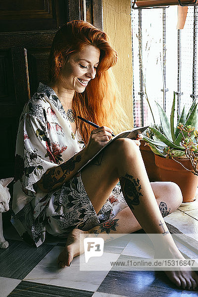 Rothaarige tätowierte Frau zu Hause  die in einem Notizbuch in der Nähe des Fensters schreibt