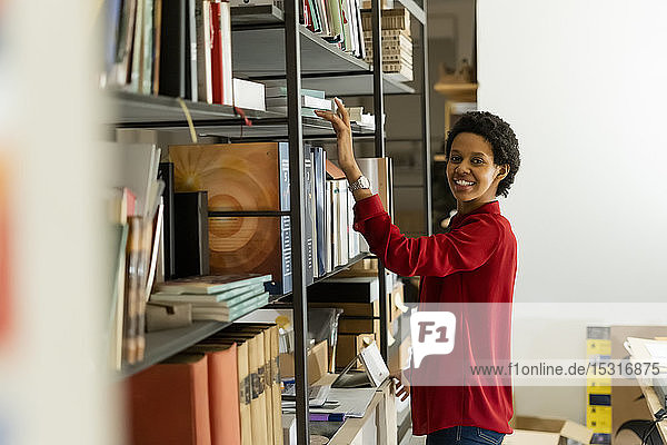 Portrait oif smiling businesswoman taking book from shelf in office