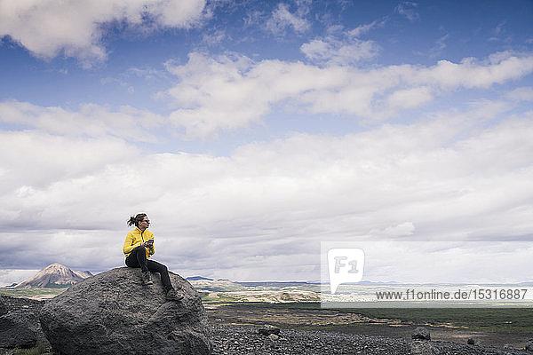 Junge Frau sitzt auf einem Felsen in Myvatn  Island  und benutzt ein Smartphone