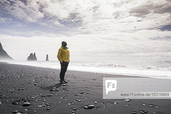 Mature man walking on a lava beach in Iceland