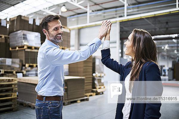 Geschäftsmann und Geschäftsfrau  die sich in einer Fabrik abrackern