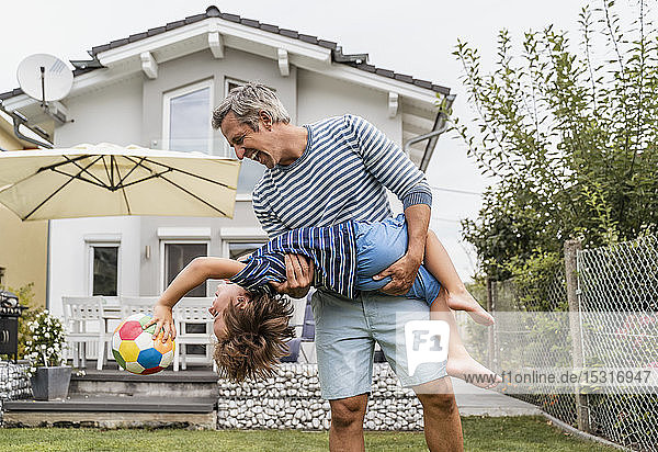 Playful father and son with football in garden