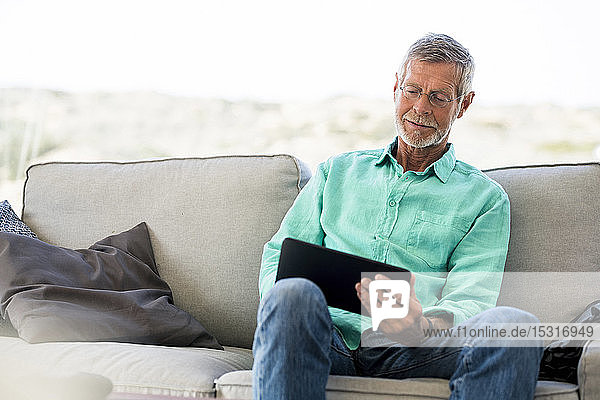 Senior man using tablet on couch at home