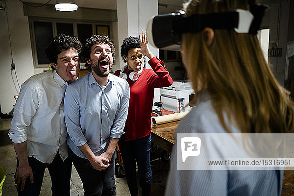 Playful colleagues looking at woman wearing VR glasses in office