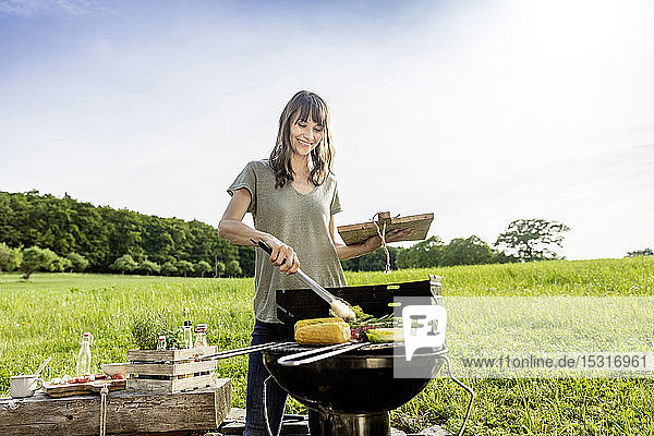 Smiling woman preparing vegetable on barbecue grill