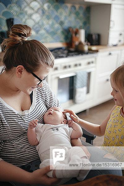 Lächelnde Frau mit ihrem Baby und ihrer älteren Tochter in der Küche