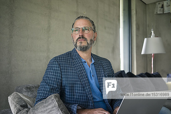 Mature businessman sitting on couch at home with laptop looking away