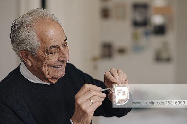 Lächelnder älterer Mann  der zu Hause eine Uhr repariert