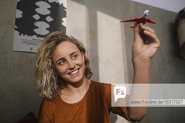 Porträt einer lächelnden jungen Frau mit Spielzeugflugzeug