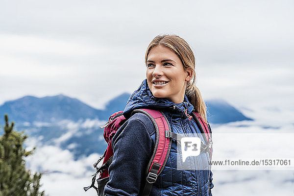 Smiling young woman on a hiking trip in the mountains  Herzogstand  Bavaria  Germany