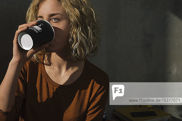 Blond young woman drinking coffee to go at home
