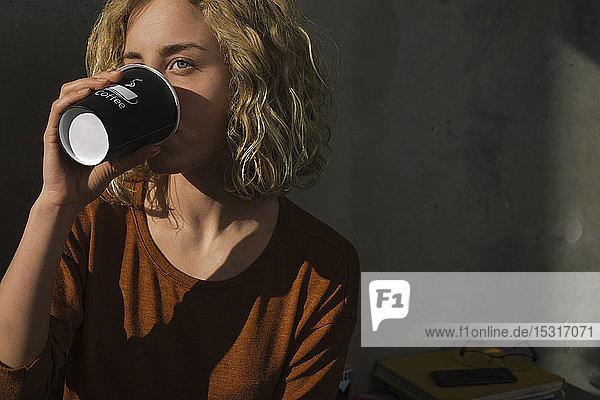 Blonde junge Frau trinkt Kaffee für zu Hause