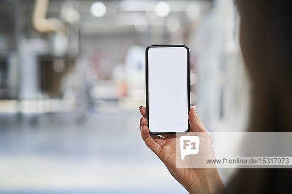 Nahaufnahme einer Geschäftsfrau mit Handy in der Fabrik