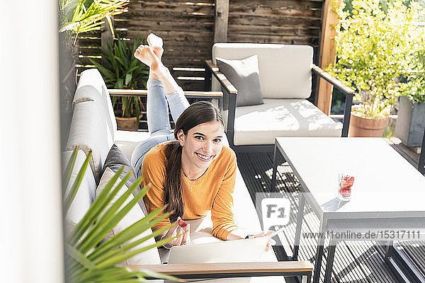 Porträt einer lächelnden jungen Frau  die mit Handy und Laptop auf der Couch auf der Terrasse liegt