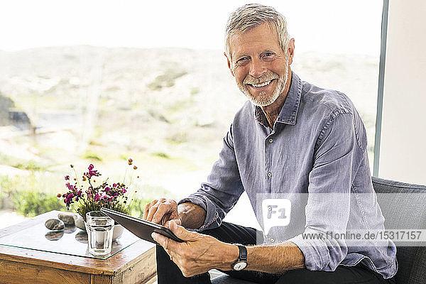 Portrait of smiling senior man using tablet at home