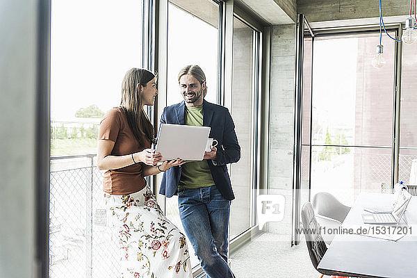 Junge Geschäftsfrau und Geschäftsmann mit Laptop am Fenster im Büro
