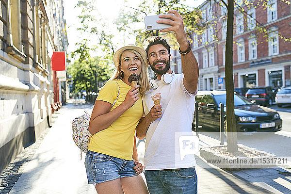 Glückliches junges Paar  das sich beim Eisessen in der Stadt ein Selfie gönnt