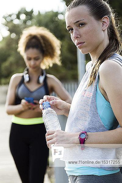 Zwei sportliche junge Frauen beenden ihr Training