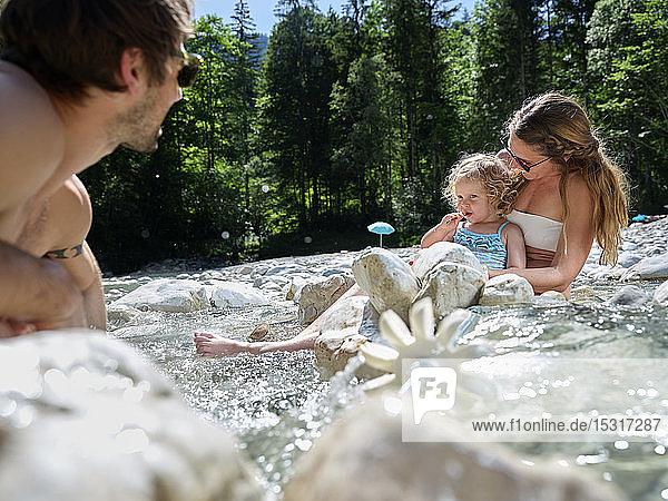 Familie mit Tochter repariert Wasserrad in einem Gebirgsbach