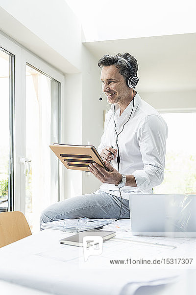 Geschäftsmann in hellem Büro bei einer Telefonkonferenz  mit Headset und digitalem Tablet