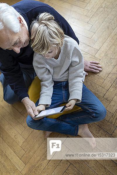 Grossvater und Enkel sitzen zu Hause auf dem Boden und benutzen ein Tablett