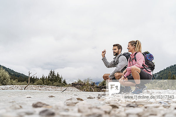 Young couple on a hiking trip crouching at riverside  Vorderriss  Bavaria  Germany