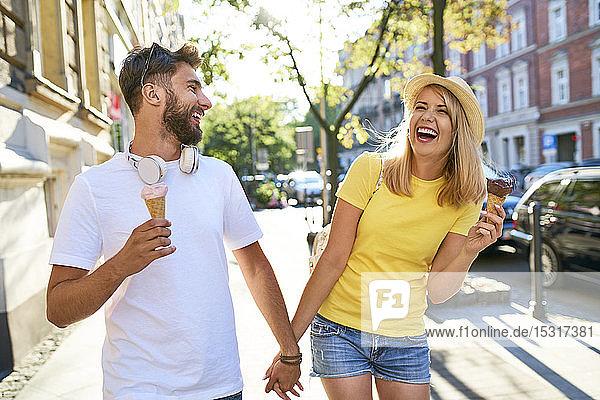 Glückliches junges Paar genießt Eiscreme in der Stadt