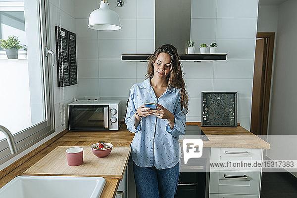 Junge Frau mit Pyjama in der Küche zu Hause am Handy