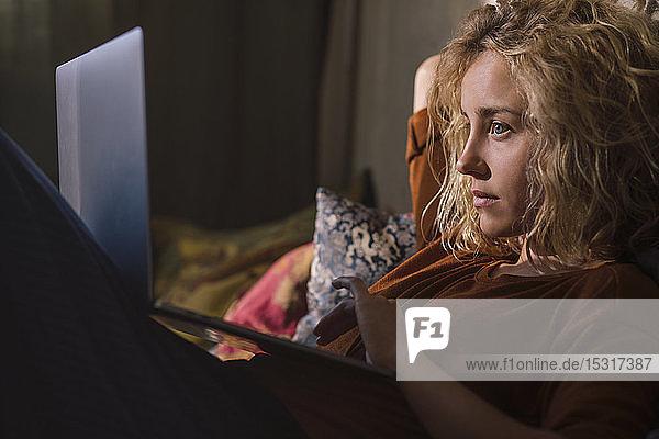 Porträt einer blonden jungen Frau  die mit einem Laptop auf dem Bett liegt