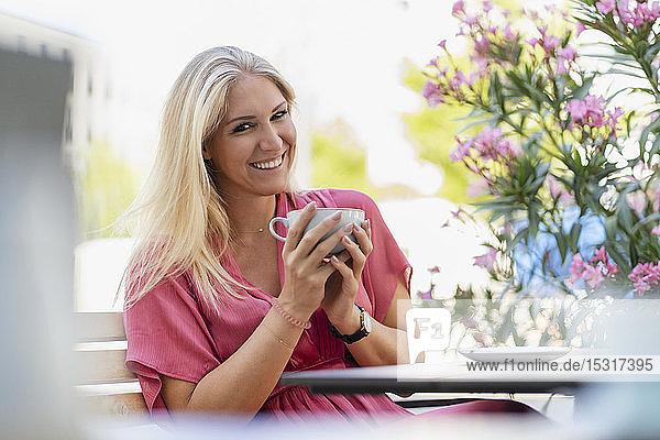 Porträt einer lächelnden blonden Frau  die im Straßencafé Kaffee trinkt