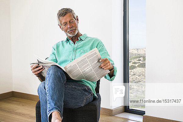 Senior man reading newspaper at home