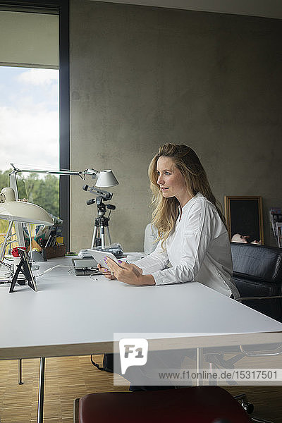 Businesswoman working at desk at home