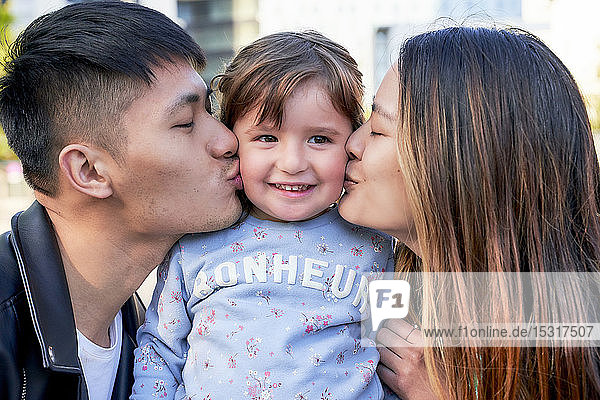 Happy parents kissing little girl