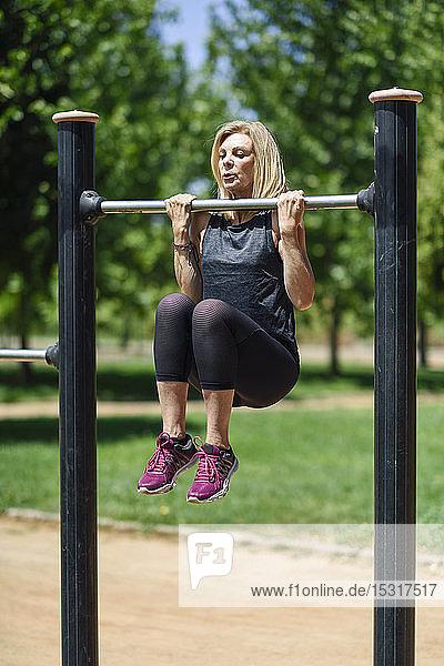 Eine reife Frau übt an einer Bar in einem Park