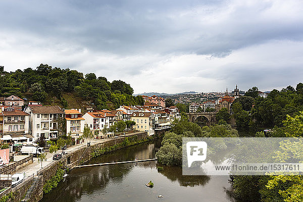 River canal by buildings in town at Duoro Valley against cloudy sky