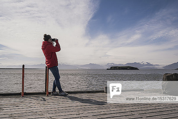 Young woman standig on a jetty  looking through binoculars  South East Iceland