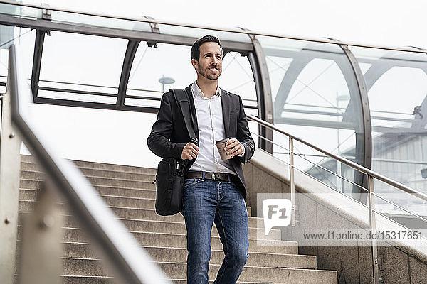 Geschäftsmann mit Kaffee zum Mitnehmen auf einer Treppe in der Stadt
