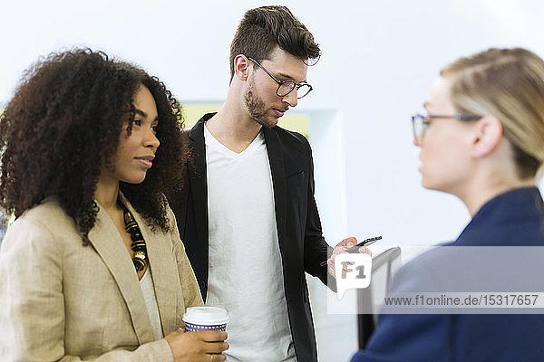 Junge Geschäftsleute mit Kaffee zum Mitnehmen und Smartphone