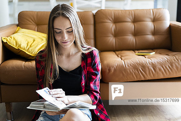 Young woman with a photo album at home