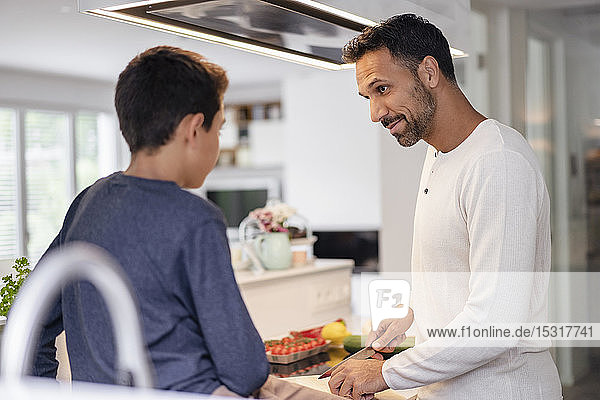 Father and son cooking in kitchen at home together