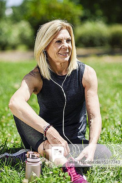 Reife Frau ruht sich nach dem Sport im Gras eines Parks aus