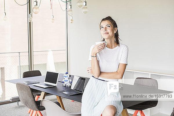Junge Geschäftsfrau macht Kaffeepause im Büro und schaut auf