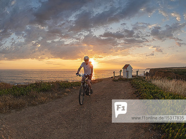 Portugal  Alentejo  senior man on e-bike at sunset