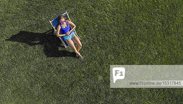 Luftaufnahme einer jungen Frau beim Sonnenbaden auf dem Rasen