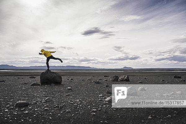 Reifer Mann balanciert auf einem Bein auf einem Felsen im vulkanischen Hochland von Island