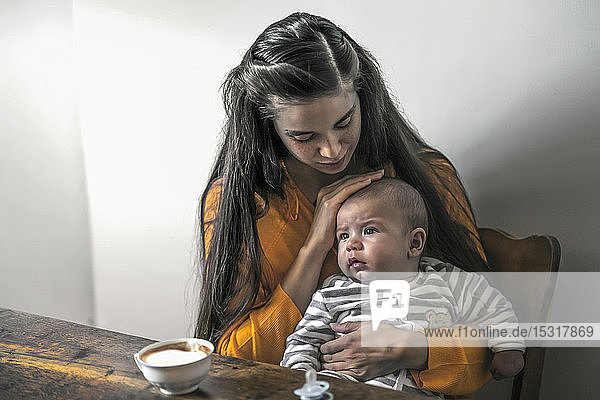 Mother with baby sitting at wooden table at home