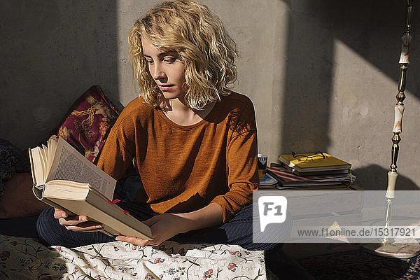 Blonde Studentin sitzt im Bett und liest ein Buch