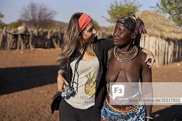 White woman and Muhacaona traditional woman embracing  Oncocua  Angola