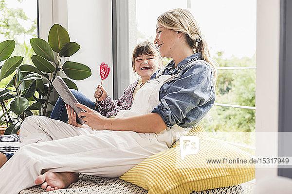 Glückliche Mutter und Tochter mit Tablette und Lolli am Fenster zu Hause